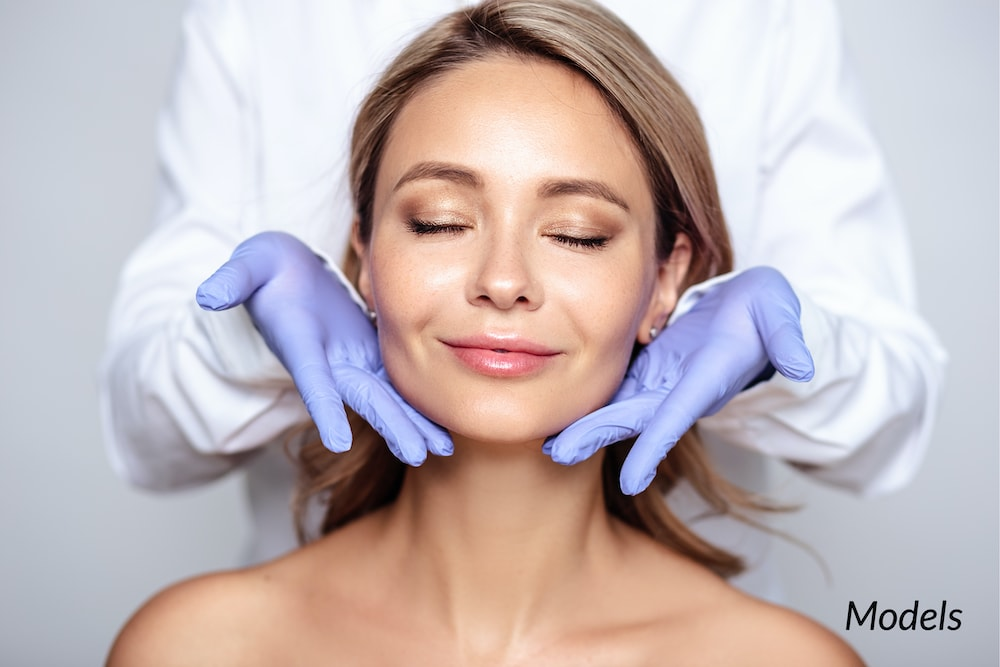 close-up of woman getting facial with dermatologist hands around face.