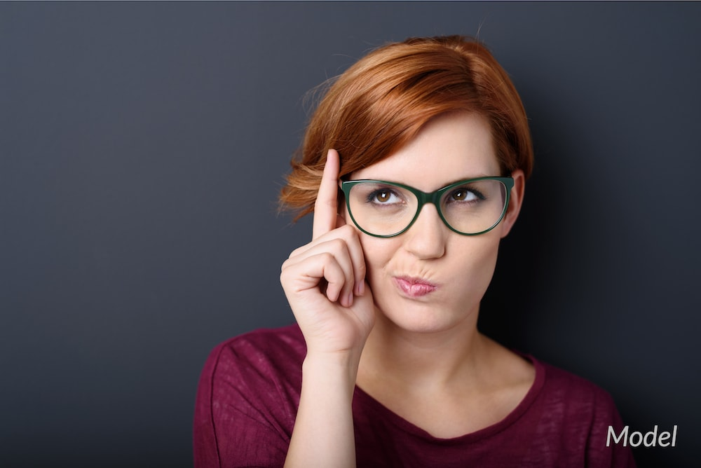 Woman with glasses thinking about her plastic surgery choices