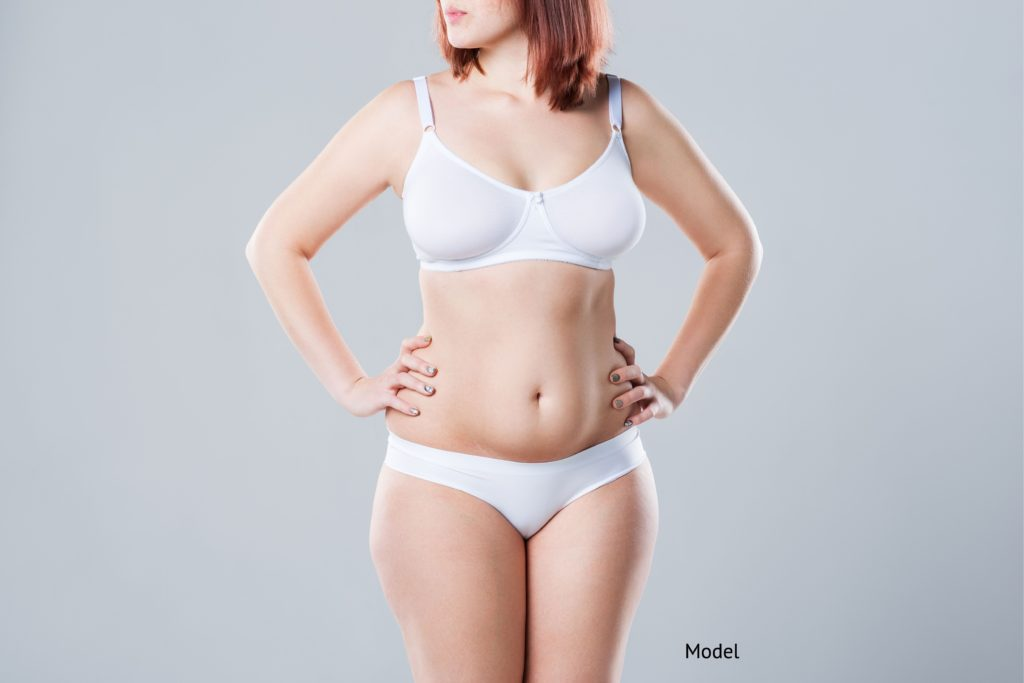 woman who is considering different methods for her tummy tuck surgery