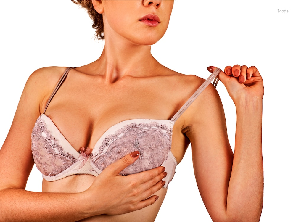 Woman with hand under her bra holing up her breast, potentially after breast augmentation.