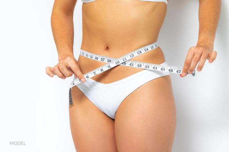 woman in white underwear measuring her waist.