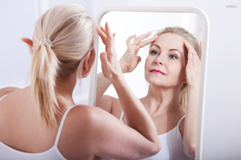 A woman examining her aging face in mirror, contemplating facelift surgery.