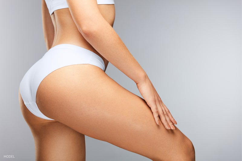 Close-up image of the back of a woman's thigh and hip wearing white underwear.