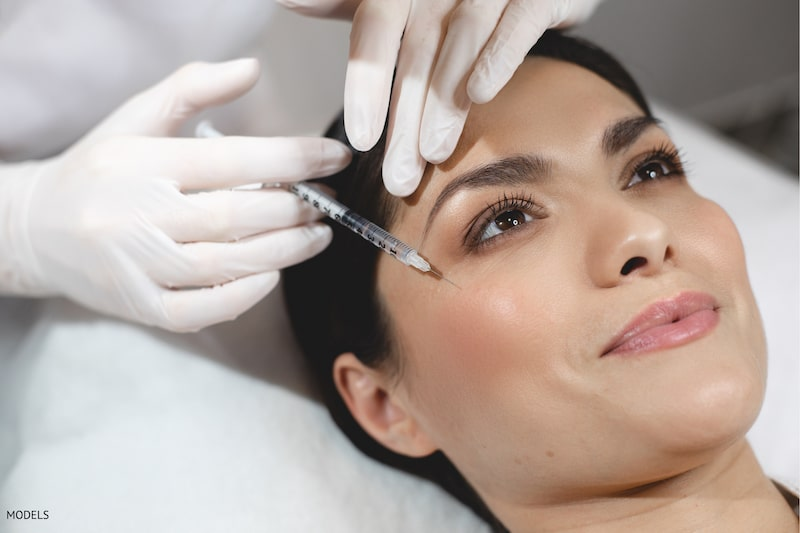 Women getting an injectable filler in the top of her cheek area by a woman in white surgical gloves.